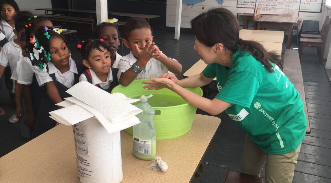 A intern demonstrates thorough handwashing during her Public Health internship in Belize for groups.